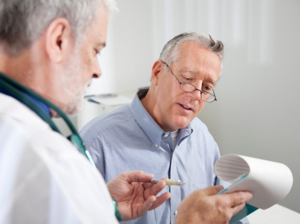 A doctor with a patient filling out paperwork on a clipboard