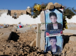 Posters of a boy, killed in Shi'ite-Sunni violence, displayed on his grave in Sanaa, Yemen, November 17, 2014