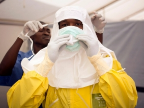 Health workers don protective gear before entering an Ebola quarantine zone at a Red Cross facility in Koidu, Sierra Leone, December 19, 2014