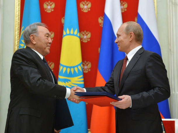 Russian President Vladimir Putin exchanges documents with his Kazakh counterpart Nursultan Nazarbayev during a meeting at the Kremlin in Moscow, December 22, 2014