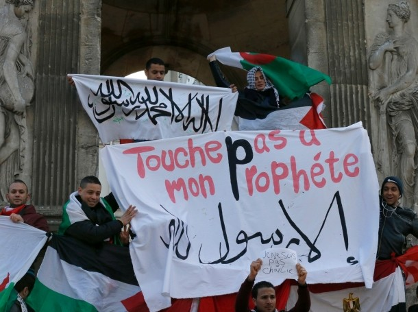 """French Muslims hold an Islamic flag and a banner reading """"Do not touch my prophet, anything but the Messenger of Allah"""" as they gather in central Paris January 18, 2015"""