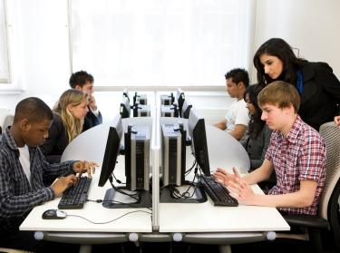 Teacher helping a high school student on a computer