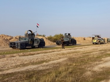 Iraqi security forces guard during the building of a new road between Diyala province and Samarra December 21, 2014. The Badr Organization, a leading political party and militia with ties to Iran, is supervising the new road.