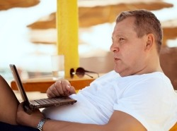 Man with a laptop at beach resort
