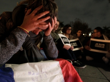 A woman with a French flag with the words 'I am Charlie' reacts while paying tribute to the victims of a shooting at the offices of French weekly newspaper Charlie Hebdo in Paris, during a candlelight vigil at the Liberty Square in Taipei, January 9, 2015
