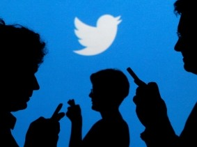 People holding mobile phones are silhouetted against a backdrop projected with the Twitter logo