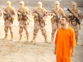 A man purported to be ISIS captive and Jordanian pilot Muath al-Kasaesbeh in front of armed men in a still image from an undated video filmed in an undisclosed location, made available on social media on February 3, 2015, Reuters/Social media via Reuters TV