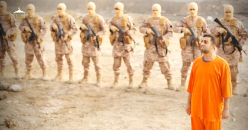 A man purported to be ISIS captive and Jordanian pilot Muath al-Kasaesbeh in front of armed men in a still image from an undated video filmed in an undisclosed location, made available on social media on February 3, 2015