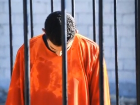 A man purported to be ISIS captive Jordanian pilot Muath al-Kasaesbeh in a cage in a still image from an undated video filmed from an undisclosed location, made available on social media on February 3, 2015