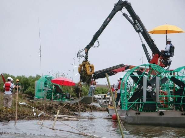 Workers remove oil-soaked grass from a marshland in Bay Jimmy, Louisiana, one year after the Deepwater Horizon oil spill, April 2011