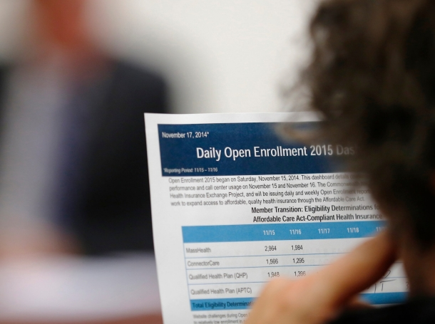 A reporter reads a summary of the performance and usage of the Massachusetts ACA health insurance exchange, Boston, November 17, 2014