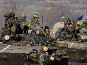 Members of the Ukrainian armed forces ride on armoured personnel carriers near Debaltseve, eastern Ukraine, February 12, 2015, photo by Gleb Garanich/Reuters