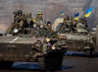 Members of the Ukrainian armed forces ride on armoured personnel carriers near Debaltseve, eastern Ukraine, February 12, 2015