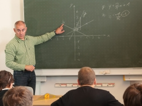 Mathematics teacher pointing to the blackboard and talking to his class, photo by thelinke/iStock