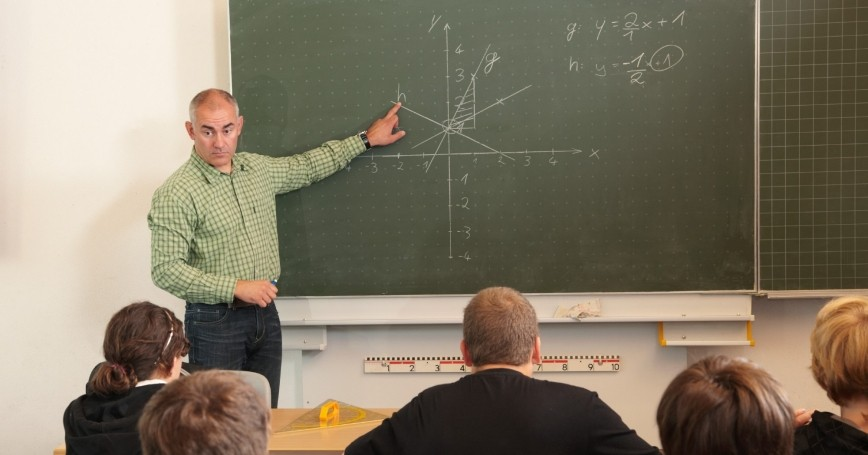 Mathematics teacher pointing to the blackboard and talking to his class