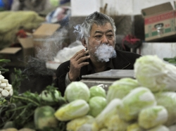 A vendor smokes a cigarette as he waits for customers at a market in Hefei, China, January 9, 2015