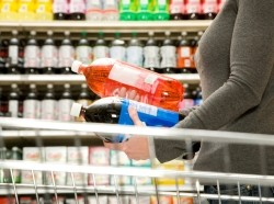 Woman comparing soda labels in a supermarket