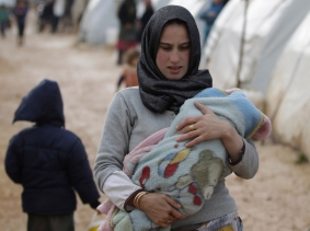 A woman carries a baby inside Al-Karameh refugee camp beside the Syrian-Turkish border, January 10, 2015
