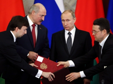 Russia's President Vladimir Putin and his Belarussian counterpart Alexander Lukashenko (2nd L) attend a signing ceremony during a session of the
