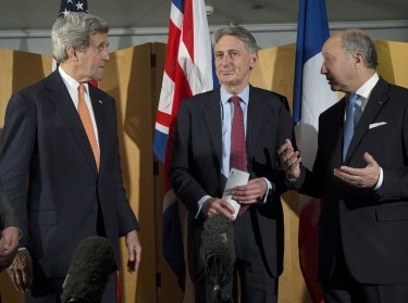 U.S. Secretary of State John Kerry, British Foreign Secretary Philip Hammond, and French Foreign Minister Laurent Fabius talk after Hammond's statement about recent negotiations over Iran's nuclear program in London on March 21, 2015