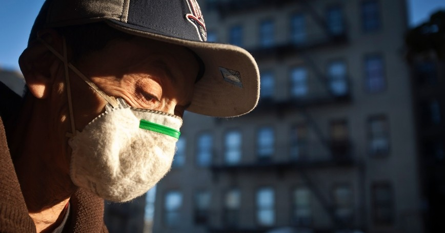 A mask-wearing man walks past an apartment building where a child was taken to the hospital to be tested for Ebola, New York City, October 27, 2014