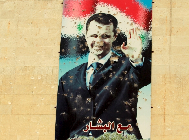 A damaged picture of Syrian president Bashar al-Assad in Idlib, March 28, 2015