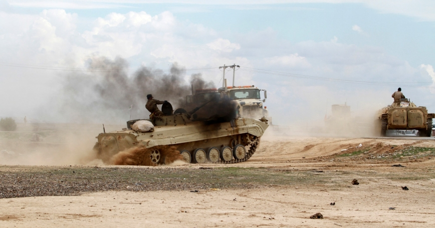 An Iraqi soldier rides in an armoured vehicle in Salahuddin province, Iraq, March 4, 2015, where Islamic State militants set fire to oil wells in the Ajil field east of the city of Tikrit to try to hinder aerial attacks aimed at driving them from the oilfield
