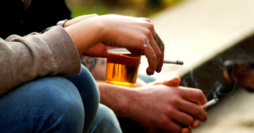 Closeup of hands of two people drinking and smoking