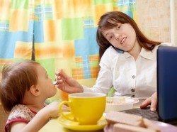 Woman feeding baby while using laptop and talking on phone