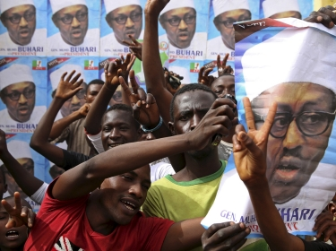 Supporters of Nigerian presidential candidate Muhammadu Buhari gesture in front of his election posters in Kano March 27, 2015