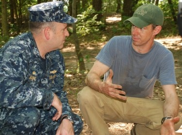 Capt. Chuck Marks, commanding officer of Naval Weapons Station Yorktown, listens to Martin Gallivan, associate professor of anthropology at the College of William and Mary, talk about the artifacts his team of students uncovered during the excavation of a Powhatan Indian village, a field study being conducted under a cooperative agreement between the Navy and the college