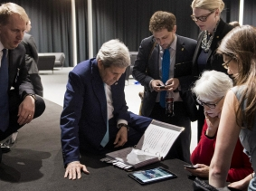 U.S. Secretary of State John Kerry and staff watch a tablet in Lausanne, Switzerland as President Barack Obama addresses the status of the Iran nuclear talks, April 2, 2015, photo by Brendan Smialowski/Pool/Reuters