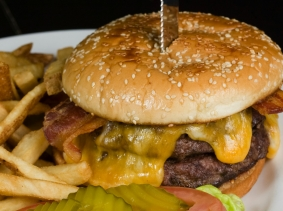 A bacon double cheeseburger with fries, pickles, and tomato on the side