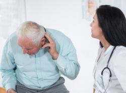 An elderly man tries explaining his pain to his doctor