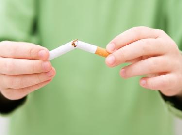 A child breaking a cigarette in half