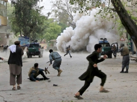 People run for cover after an explosion in Jalalabad April 18, 2015