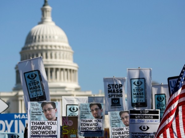 Demonstrators hold up their signs during the Stop Watching Us: A Rally Against Mass Surveillance march near the U.S. Capitol in Washington, October 26, 2013