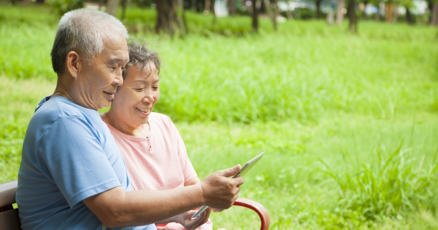 Senior couple on a park bench looking at a tablet