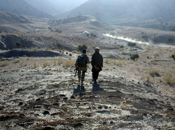 An Afghan border policeman escorts a detained suspected Taliban fighter near Walli Was in Paktika province near the border with Pakistan November 5, 2012