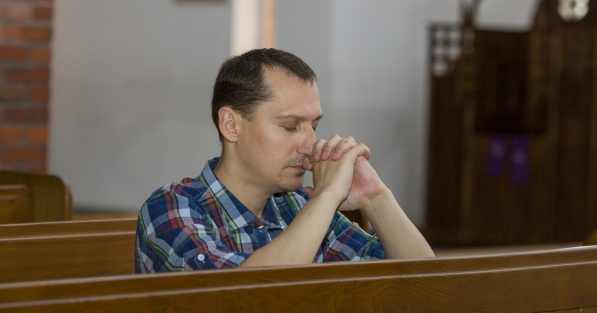 A young man praying in a church pew
