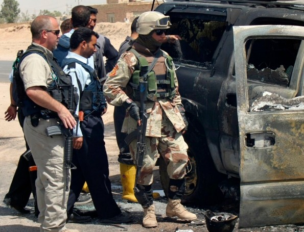 A private security contractor and soldiers look at a destroyed vehicle after an attack near Najaf, Iraq, May 18, 2006