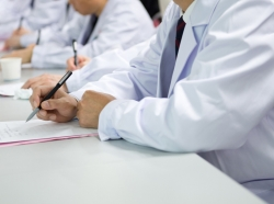 Doctors writing at a conference