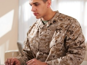Man wearing camouflage using a laptop