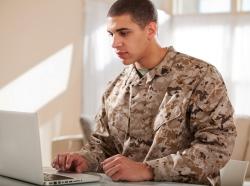 Man wearing camouflage using a laptop