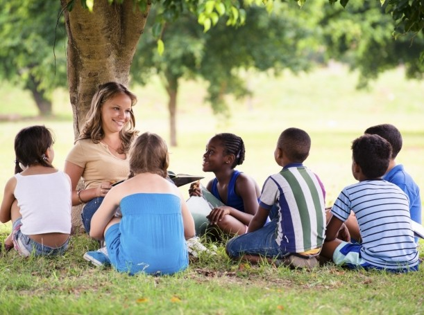 Students sitting outside under a tree with their teacher
