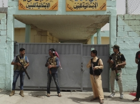 Sunni tribal fighters stand guard near a school used as a shelter for displaced people in the city of Ramadi, April 11, 2015, photo by Stringer/Reuters