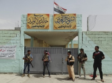 Sunni tribal fighters stand guard near a school used as a shelter for displaced people in the city of Ramadi, April 11, 2015