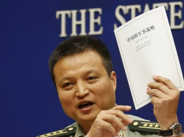Senior Colonel Yang Yujun holds a copy of the annual white paper on China's military strategy, Beijing, China, May 26, 2015