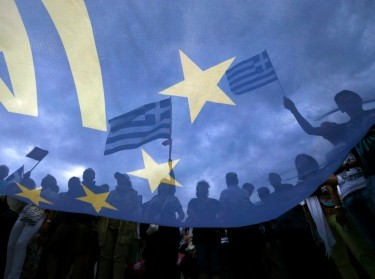 Pro-Euro protestors hold Greek national flags during a rally in front of the parliament building, in Athens, Greece, June 30, 2015