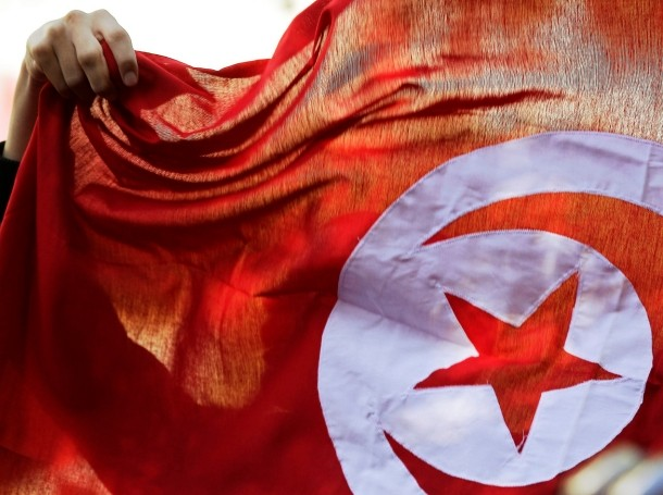 A Tunisian holds up a flag during celebrations marking the fourth anniversary of Tunisia's revolution, Tunis, January 14, 2015